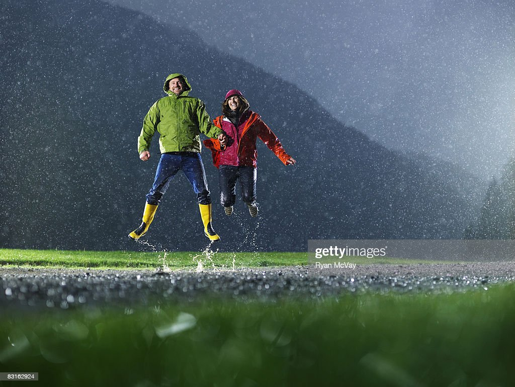 Man and woman jumping in the rain. : Stock Photo