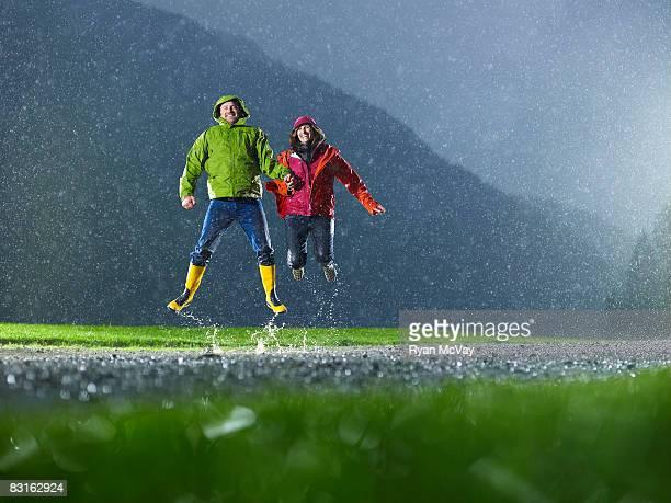 Hombre y mujer salto en la lluvia.