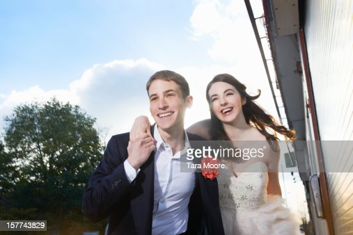 man and woman laughing and running in street : Stock Photo