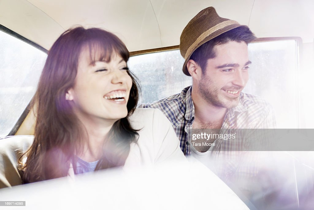 man and woman laughing in car : Stock Photo