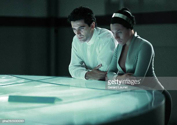 Man and woman leaning on round table