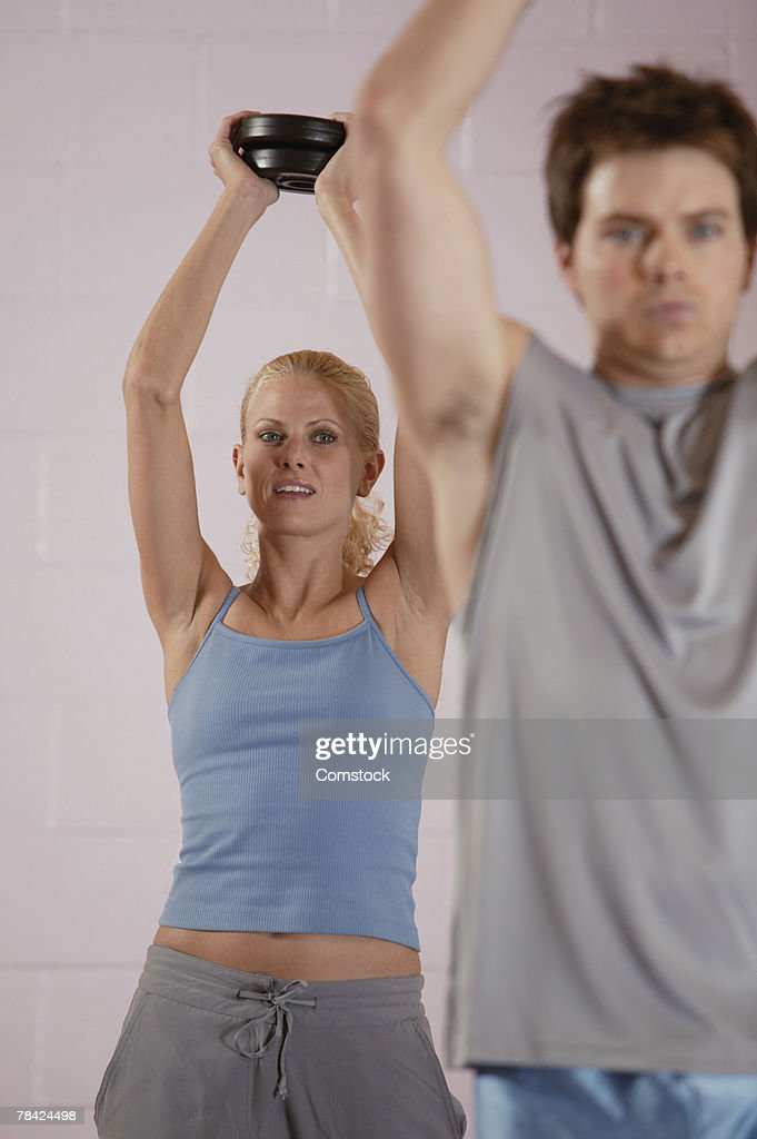 Man and woman lifting weights : Stock Photo