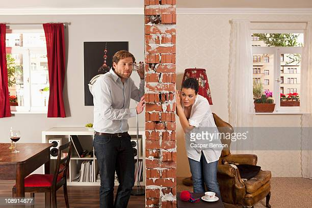 Man and woman listening on either side of wall with drinking glasses