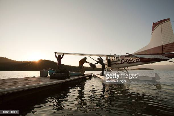 Man and woman loading luggage onto float plane