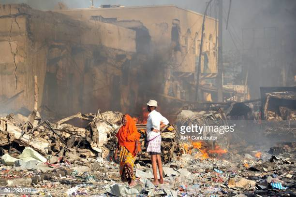 TOPSHOT A man and woman look at the damages on the site of the explosion of a truck bomb in the centre of Mogadishu on October 14 2017 A truck bomb...