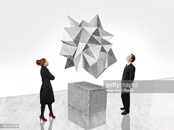 Man and woman looking at abstract art in gallery