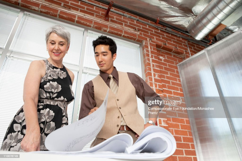Man and woman looking at architectural plans. : Stock Photo