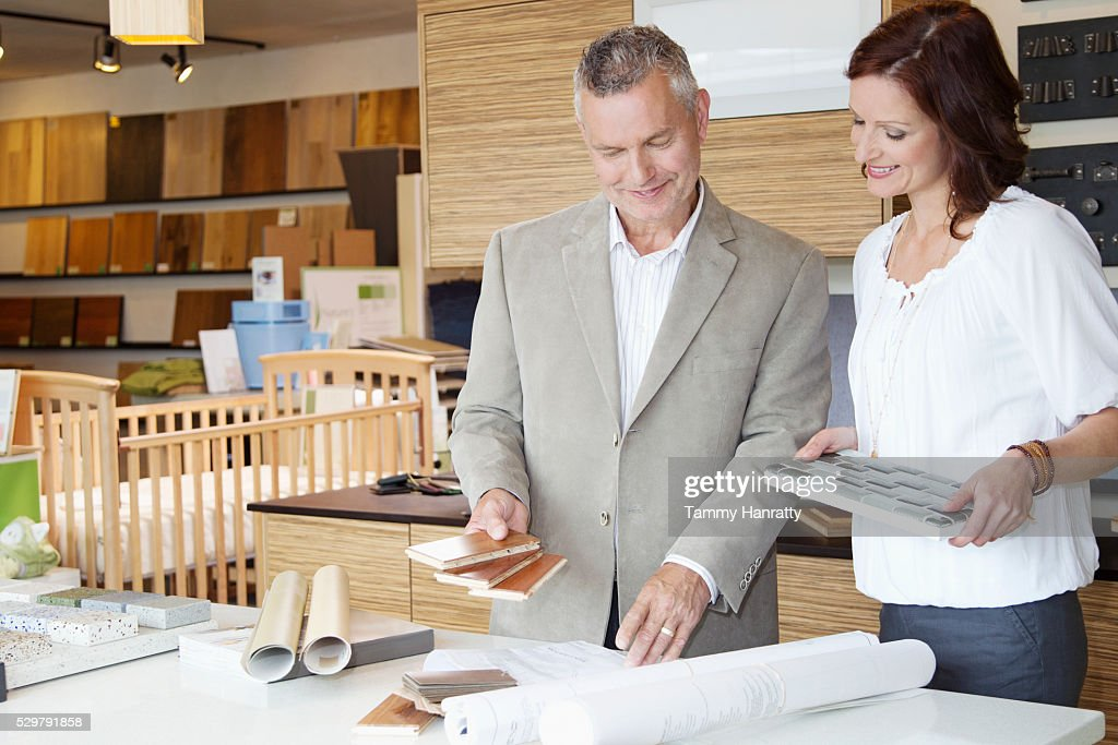 Man and woman looking at blueprints : Foto de stock