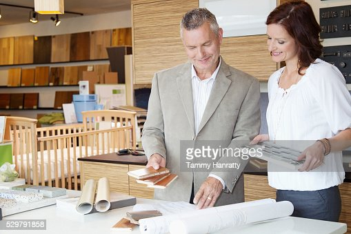 Man and woman looking at blueprints : Stock Photo