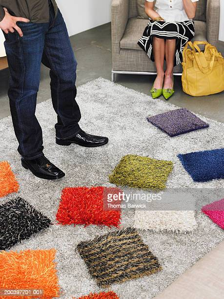 Man and woman looking at carpet samples in retail store, low section