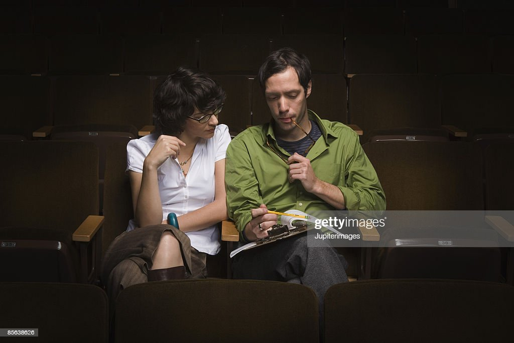 Man and woman looking at clipboard in theater