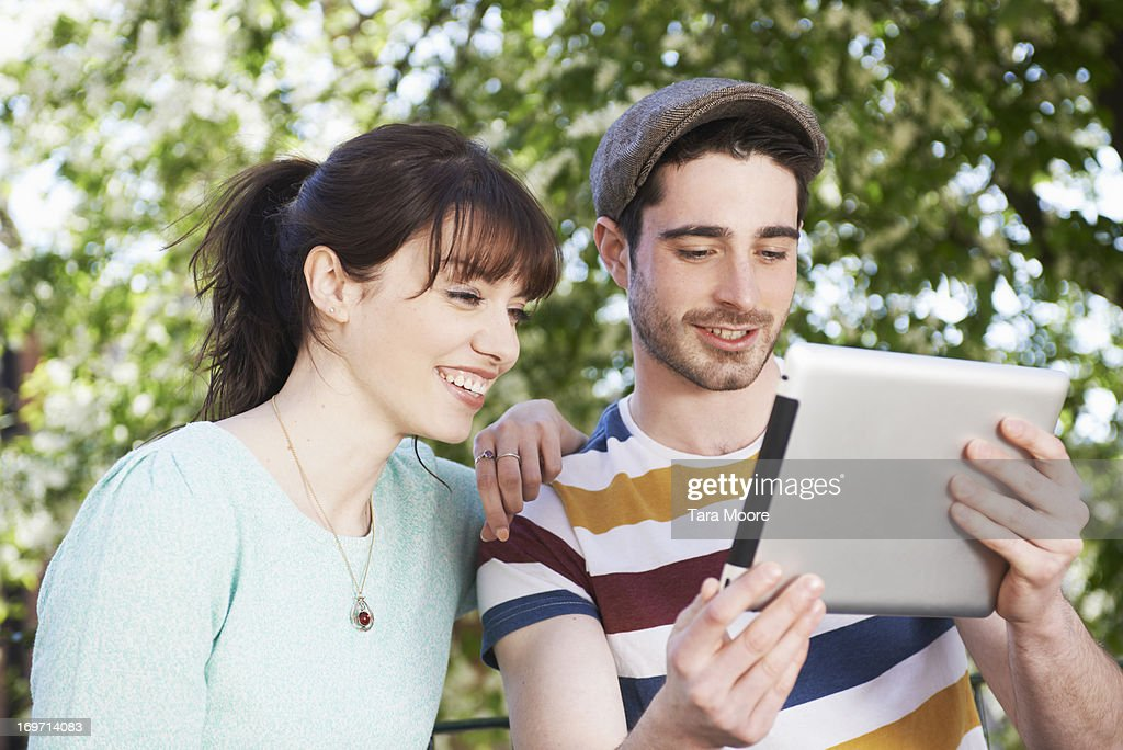 man and woman looking at digital tablet in park : Stock Photo