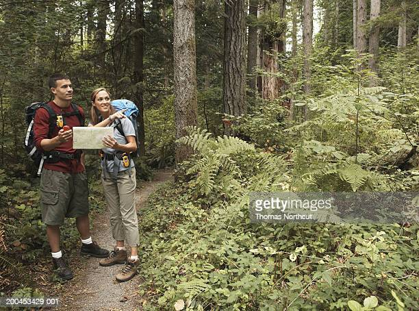 Man and woman looking at map and using GPS on footpath in forest