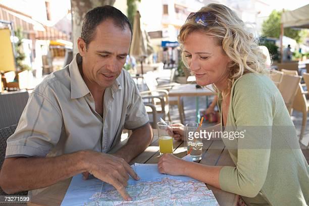 Man and woman looking at map at outdoor restaurant