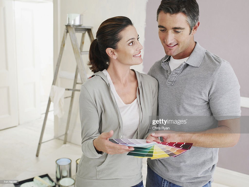 Man and woman looking at paint samples in room with ladder : Stock Photo