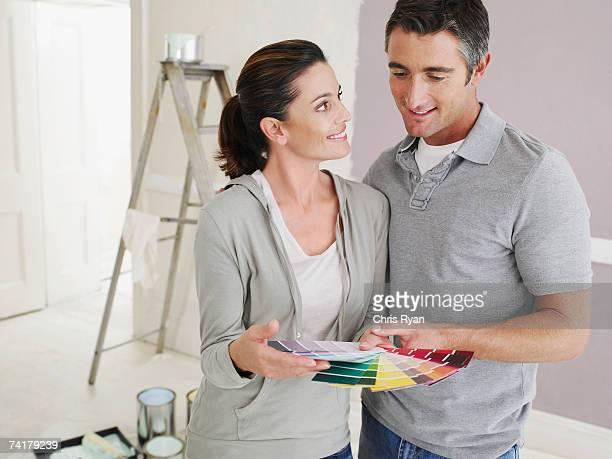 Homme et Femme regardant des échantillons de peinture dans la chambre