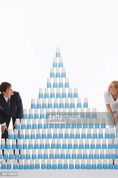 Man and Woman Looking at Pyramid of Cups