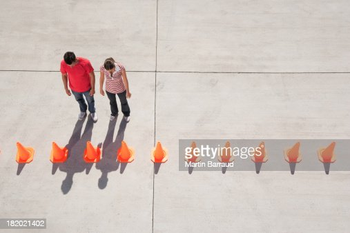 Man and woman looking at row of traffic cones
