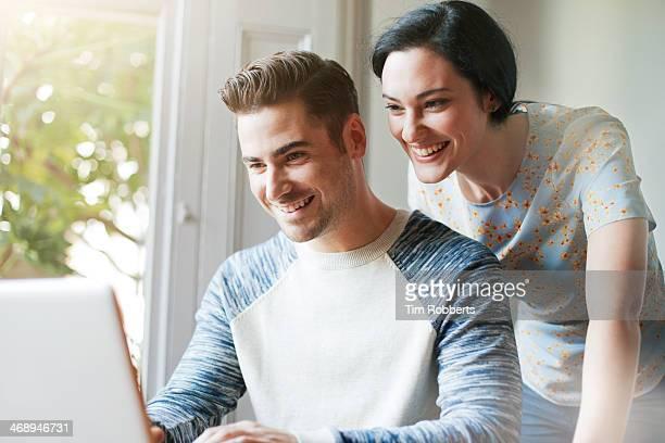 Man and woman looking at screen.