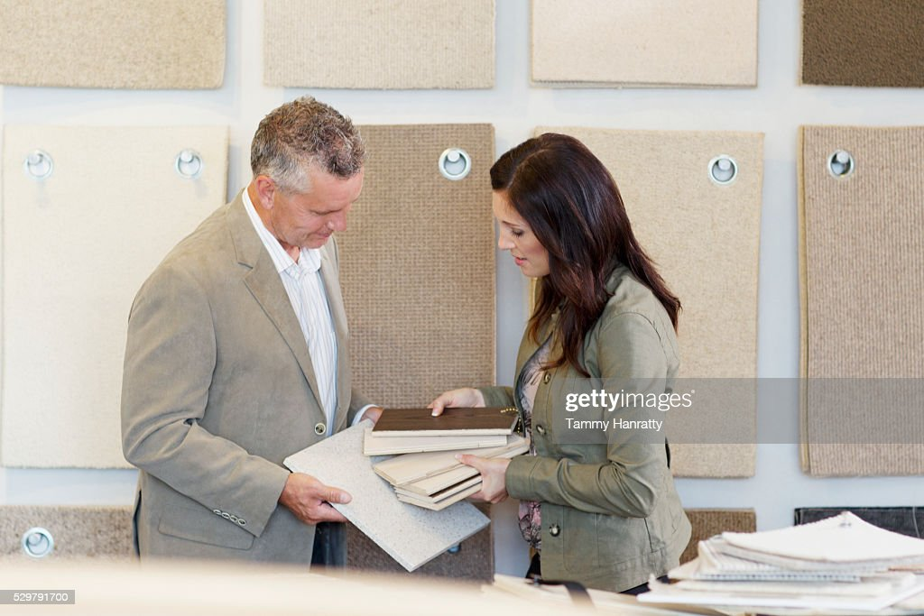 Man and woman looking at textile samples : Stock Photo