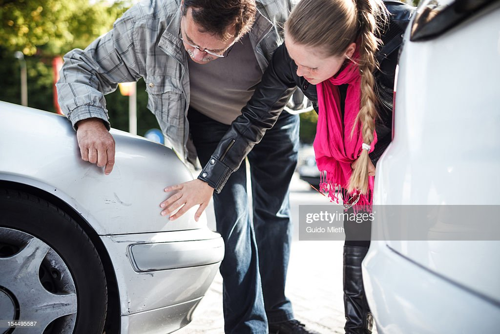 Man and woman looking car after accient.