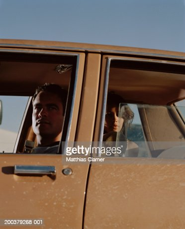 Man and woman looking out windows of car, close-up : Stock Photo