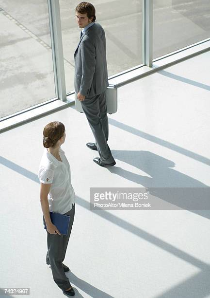 Man and woman looking over shoulders at each other, full length, high angle view