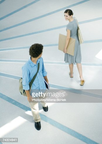 Man and woman looking over shoulders at each other in passing, full length, high angle view