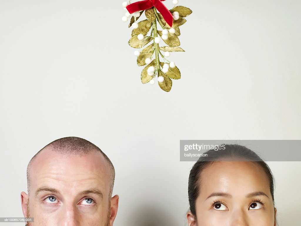 Man and woman looking up at mistletoe, high section