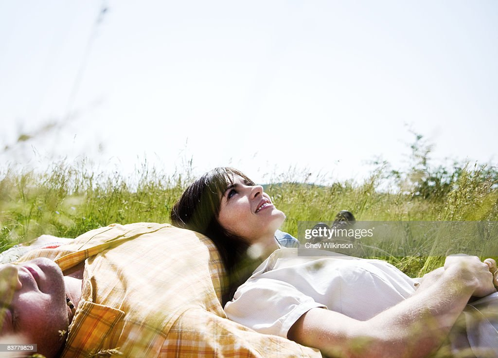 Man and woman lying in grass : Stock Photo