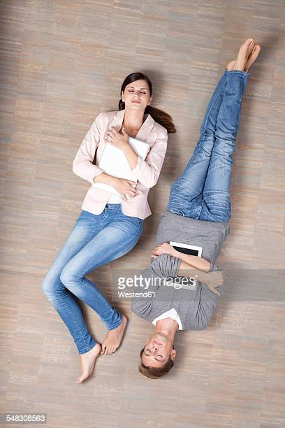 Man and woman lying on floor with laptop and digital tablet