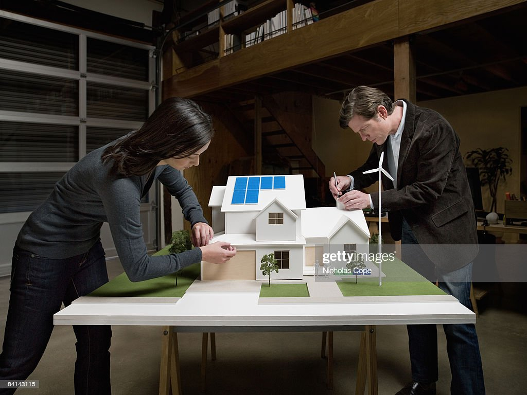 Man And Woman Make Tweaks On Architectural Model Stock Photo