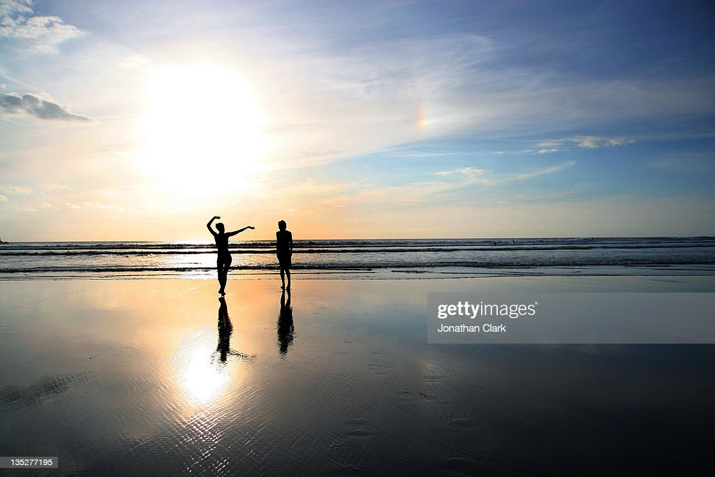 Man and woman on beach at sunset : Stock Photo