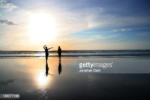 Man and woman on beach at sunset