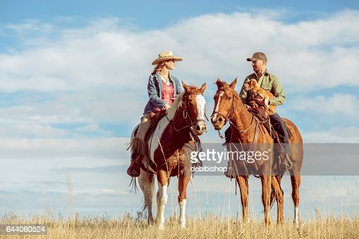 Man And Woman On Horseback Looking At Each Other