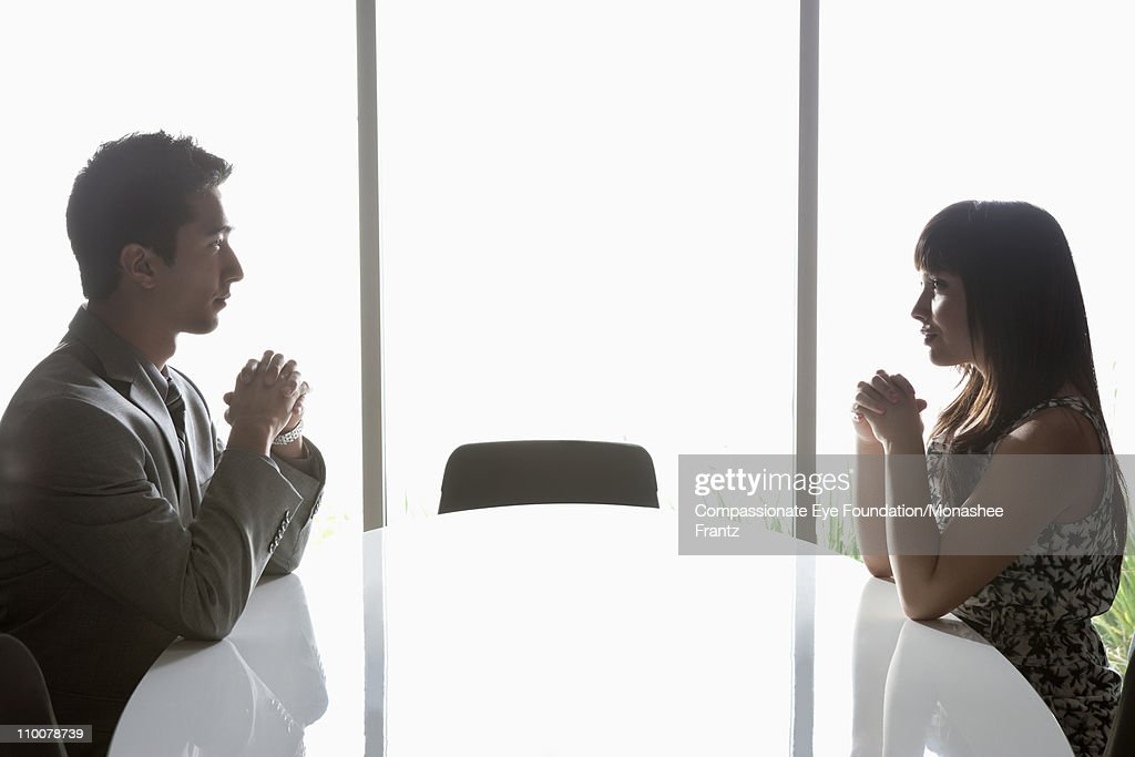 Man and woman on opposite sides of boardroom table : Stock Photo