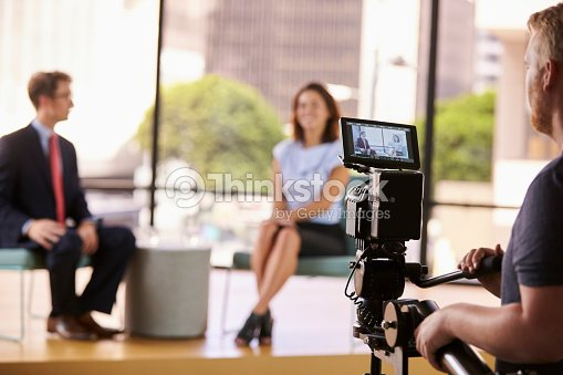 Man and woman on set for a TV interview, focus on : Stock Photo