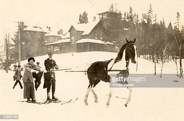 A man and woman on skis are dragged by a horse through the snow at the bottom of a hill on which sits a large building at the Lake Placid Club Lake...