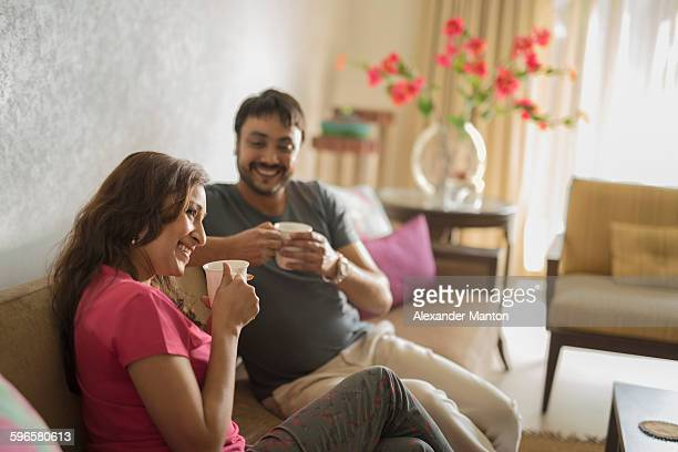 Man and woman on sofa holding coffee cups smiling