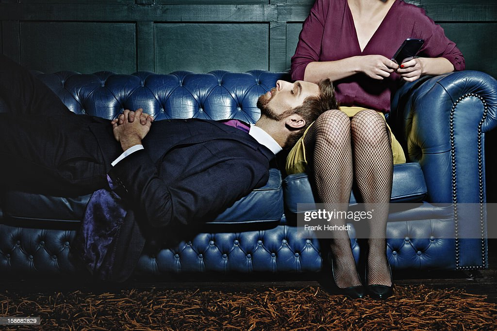Man and woman on sofa. Woman holding phone : Stock Photo