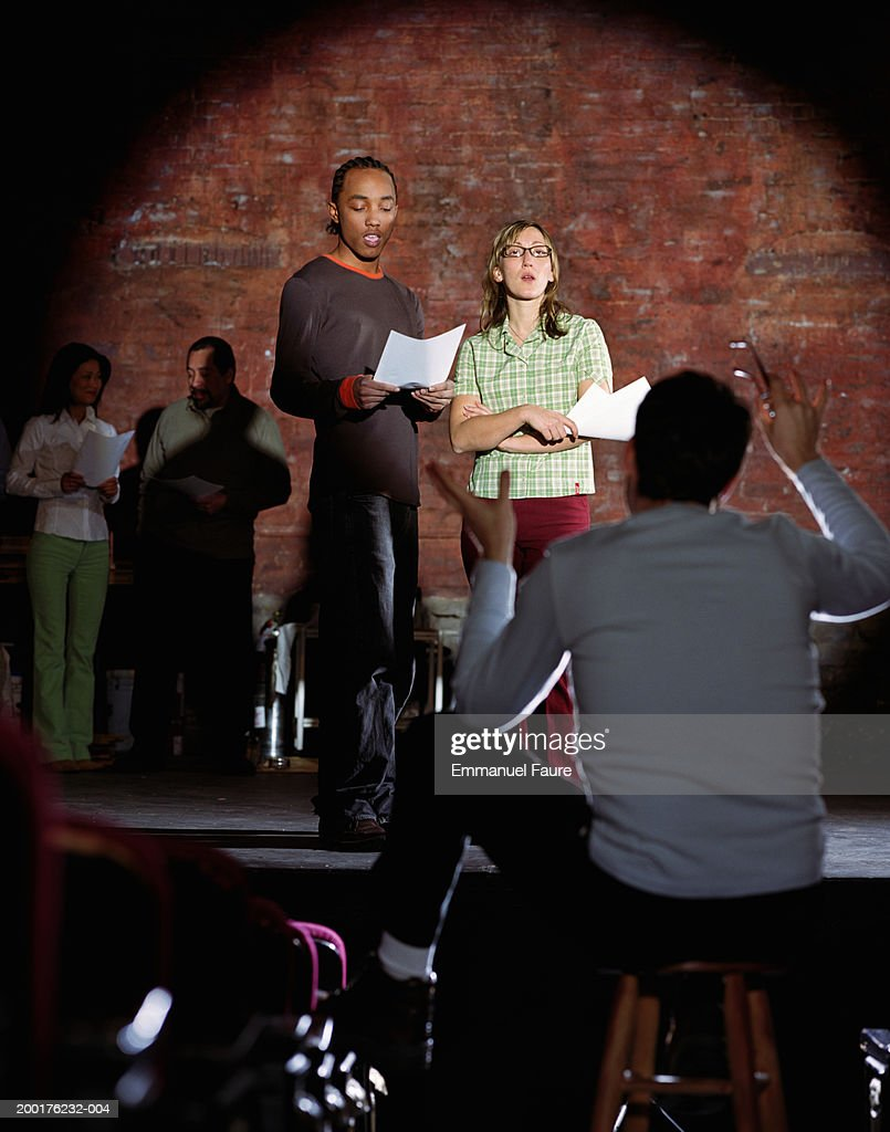 Man and woman on stage auditioning with director