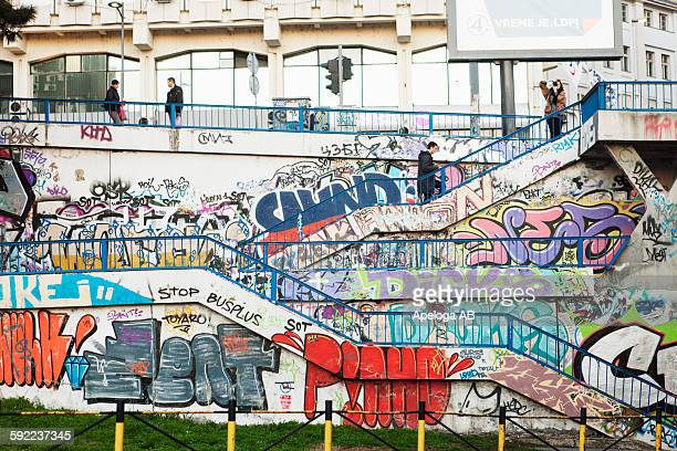 Man and woman on steps with graffiti