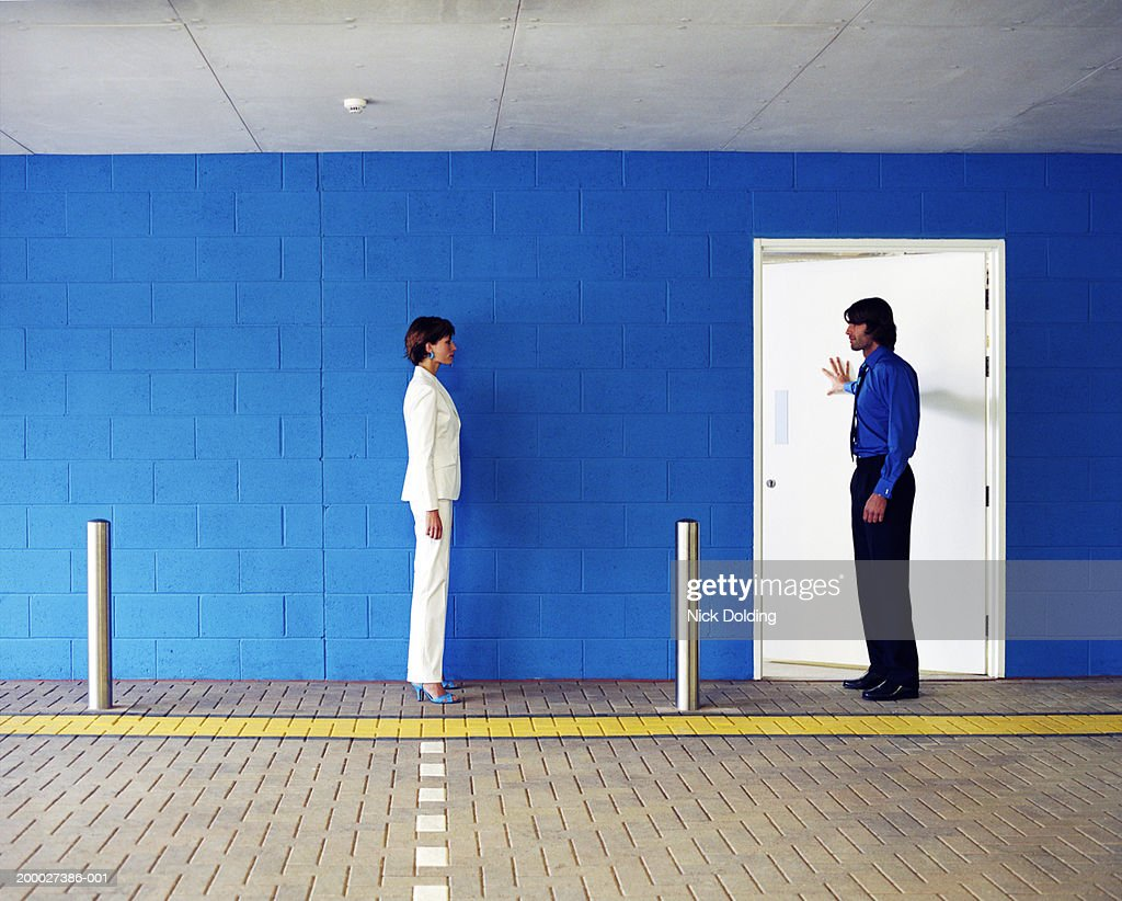 Man and woman opposite each other in car park, man pushing door open : Stock Photo