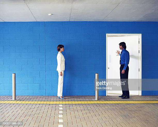 Man and woman opposite each other in car park, man pushing door open