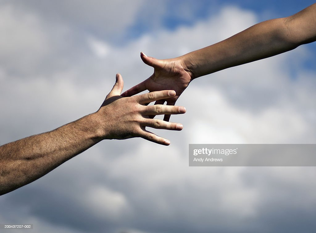 Man and woman outdoors reaching out hands, close-up : Stock Photo