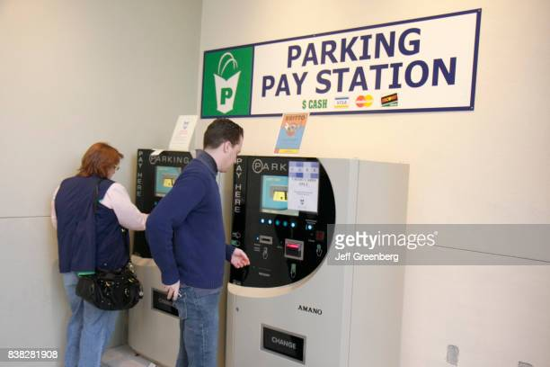 A man and woman paying at the parking pay stations at a garage in Midtown Miami