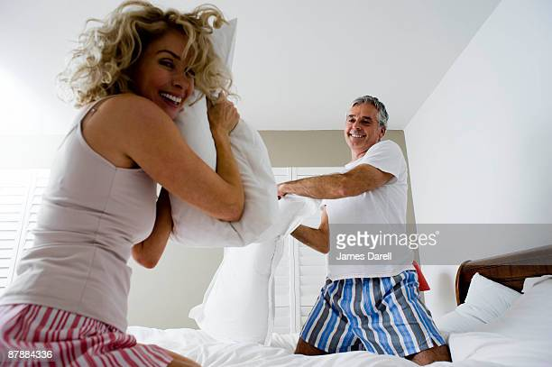 Man and woman pillow fighting