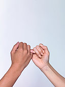 Man and woman pinky-swearing, close-up of hands