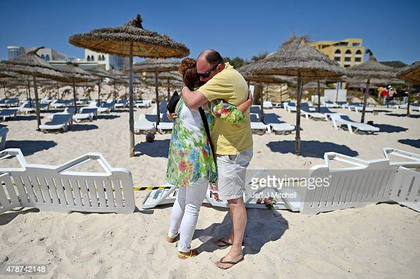 A man and woman place flowers at the beach next to the Imperial Marhaba Hotel where 38 people were killed yesterday in a terrorist attack on June 27...