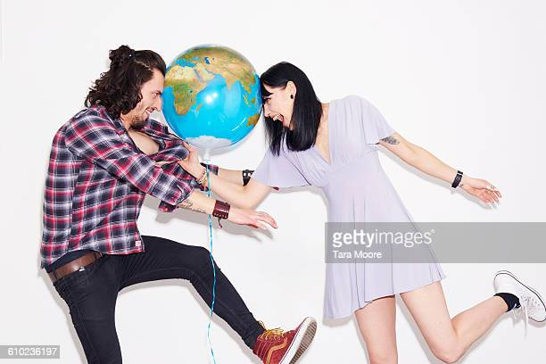 man and woman play fighting with world balloon